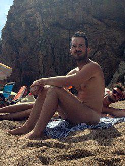 Naked guys hugging on the beach