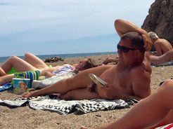 An elderly nudist sunbathes and reads a...