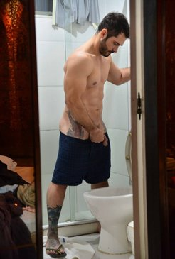 Muscled guy with tattoos pee in toilet